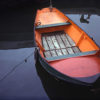 Brightly painted (orange/red) rowboat floats in oily water with reflected figures.