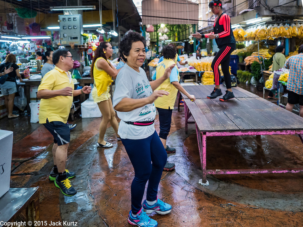 "21 DECEMBER 2015 - BANGKOK, THAILAND: People participate in an aerobics class in Pak Khlong Talat, also called the Flower Market. The market has been a Bangkok landmark for more than 50 years and is the largest wholesale flower market in Bangkok. Aerobics classes and fitness programs are common in Thai markets and parks. A recent renovation resulted in many stalls being closed to make room for chain restaurants to attract tourists. Now Bangkok city officials are threatening to evict sidewalk vendors who line the outside of the market. Evicting the sidewalk vendors is a part of a citywide effort to ""clean up"" Bangkok.       PHOTO BY JACK KURTZ"