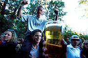 A man sitting on the shoulders of another while a hand holds a glass of beer up to the camera. Quart festival, Kristiansands Norway 2000