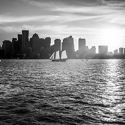 Boston skyline sunset black and white photo. Picture includes Boston skyscraper buildings and boats on Boston Harbor