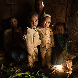 The family and neighbors of Awol Abagojam   enjoy a traditional coffee ceremony inside their mud hut in the village Choche, in Jimma, (once the capital of the region known as Kaffa) . Ethiopia boasts the most ancient and compelling traditions for coffee consumption that the world has ever seen. Coffee permeates the cultural fabric of Ethiopian life and it unites the country. It binds the many different ethnic groups together, Christian or Muslim, rich or poor. An elaborate extension to Ethiopia's warm sense of hospitality, the coffee ceremony is a daily social ritual to honour the importance of the bean, and strengthen human bonds.