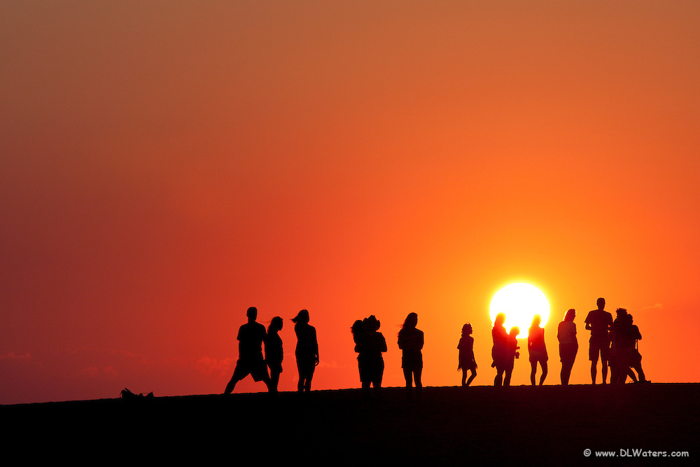 A group of people watching the sunset on top of Jockey's Ridge.