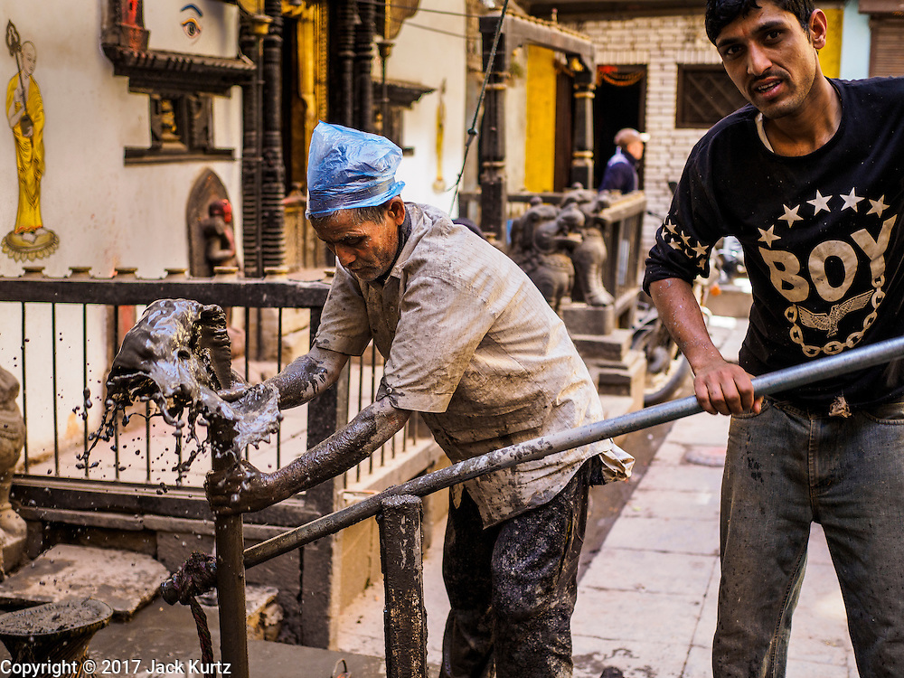 05 MARCH 2017 - KATHMANDU, NEPAL: Workers repair a water line damaged in the 2015 earthquake in front of a Buddhist temple in Kathmandu. Much of Kathmandu is now a construction site because of rebuilding  two years after the earthquake of 25 April 2015 that devastated Nepal. In some villages in the Kathmandu valley workers are working by hand to remove ruble and dig out destroyed buildings. About 9,000 people were killed and another 22,000 injured by the earthquake. The epicenter of the earthquake was east of the Gorka district.     PHOTO BY JACK KURTZ