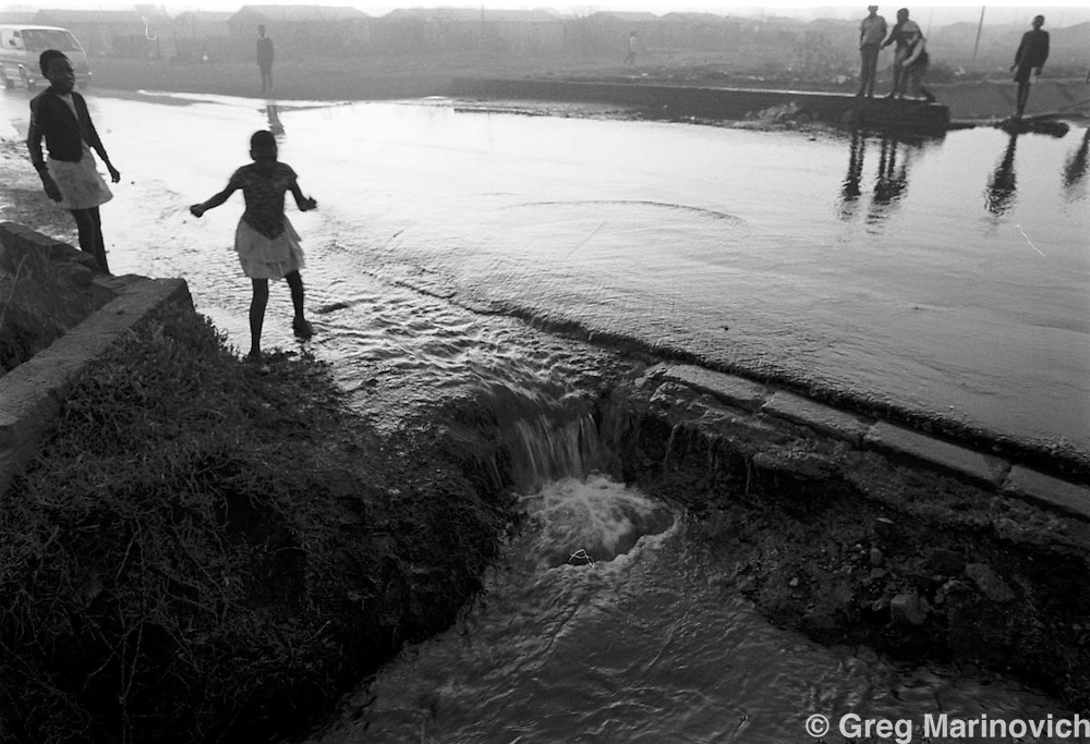 Residents try to avoid overspilling sewerage as a taxi minibus crosses a bridge in Sebokeng some 65 km south of Johannesburg, South Africa 1993. (Photo by Greg Marinovich)