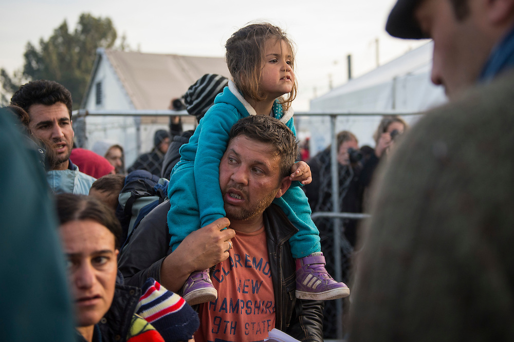March 5, 2016 - Idomeni, Greece:  A man and his daughter  after hours of waiting at the  Idomeni border crossing in Greece just before crossing to Macedonia. 12,000 refugees are stuck here after Macedonia closed the border. New arrivals come in every day, making living conditions more and more difficult. (Steven Wassenaar/Polaris)
