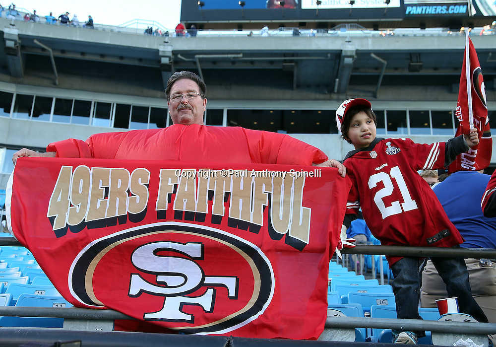 A couple of San Francisco 49ers fans hold signs and enjoy the win after the NFC Divisional Playoff NFL football game against the Carolina Panthers on Sunday, Jan. 12, 2014 in Charlotte, N.C. The 49ers won the game 23-10. ©Paul Anthony Spinelli