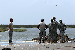 13 May 2010. Elmer Island, Lafourche Parish, Louisiana. <br /> Louisiana National guardsmen inspect sandbags deposited earlier and already disappearing fast with the tide. Like King Canute before them, Louisiana National Guardsmen of the 922nd Horizontal Engineer Company, 769th Engineer Battalion fight a losing battle against mother nature as they battle against the strong currents to close the inland waterways from the ocean now depositing oil from the Deepwater Horizon catastrophe on the beaches. <br /> Photo credit;Charlie Varley/varleypix.com