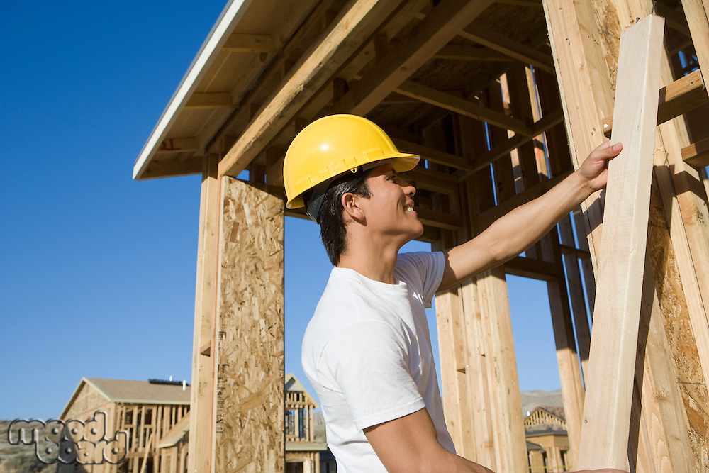 Construction worker holding wooden beam