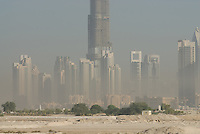 Burj Dubai tower by architecture firm SOM, sores above the rest of the buildings in a pollution haze. Dubai, one of the seven emirates and the most populous of the United Arab Emirates sits on the southern coast of the Persian gulf.