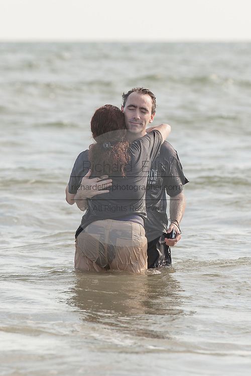 Members of the Christian Evangelical Seacoast Church hug after being baptized in the Atlantic Ocean September 11, 2011 on the Isle of Palms, South Carolina.