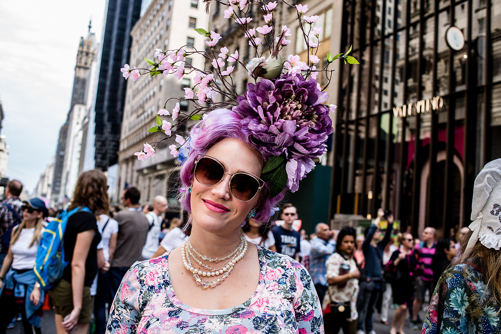 New York, NY - April 16, 2017. A woman with hair dyed purple wears a hat with a huge purple flower and sprays of pink buds  at New York's annual Easter Bonnet Parade and Festival on Fifth Avenue.