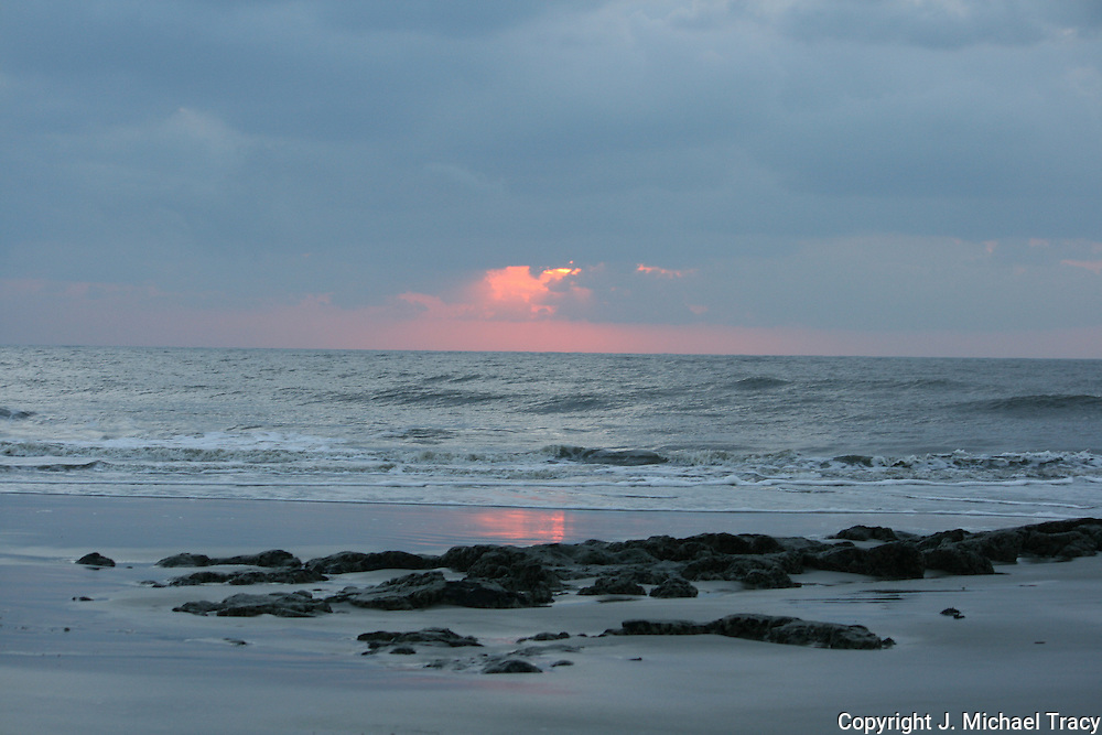 Firey sunrise on a Jekyll Island Beach with partially exposed coral rock at low tide.