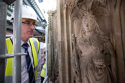 © Licensed to London News Pictures. 07/02/2018. WINCHESTER, UK. Project manager Greg Hamilton looks at  a statue of Queen Victoria on the Great Screen at Winchester Cathedral, Hampshire, as conservators are going through a spring clean removing dirt and dust from the 540-year-old stonework using soft brushes and hand-held vacuum cleaners as part of a programme of urgent repairs to the Cathedral's presbytery which has been carried out over the last three years. According to Cathedral records, this will be the first time that the Great Screen has been cleaned since the 1890s. Photo credit: ISABEL INFANTES/LNP