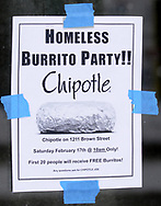 A poster taped to the window promotes a burrito party for the homeless hosted by U.D. Religious Studies student Joe Melendrez at Chipotle's on Brown Street in Dayton.