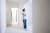 Woman leans on archway of new apartment
