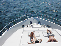 Young couple sunbathing on bow of yacht at sea elevated view