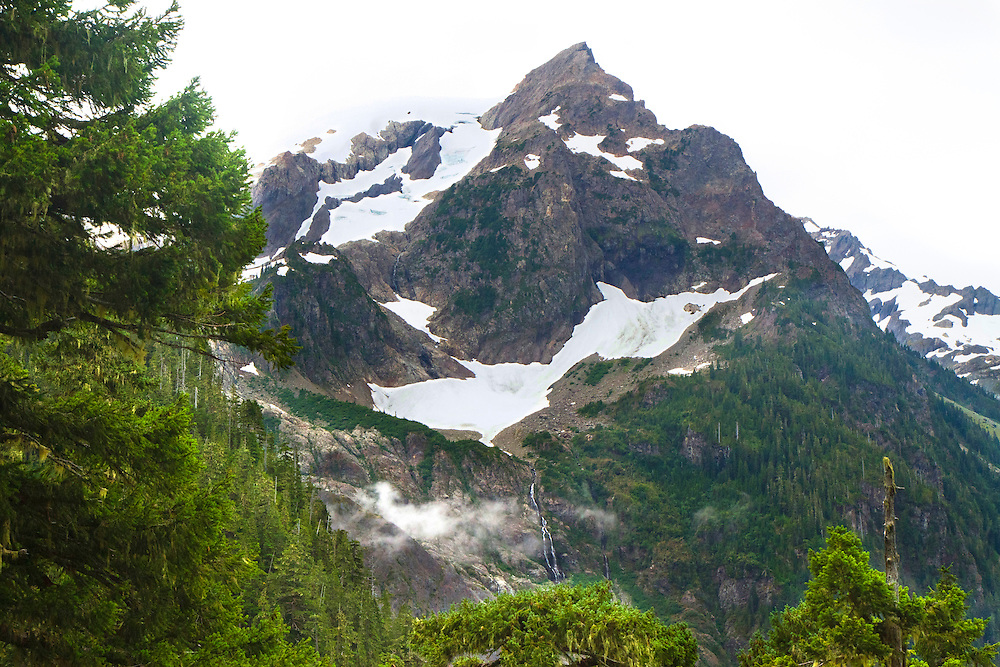 Jagged peaks along the Hoh River Trail. The Hoh River trail in Olympic National Park starts in the mossy and lush Hoh Rain Forest. From there you climb over 5,000 ft. in elevation along towering trees and rock to overlook the windswept Blue Glacier on Mt. Olympus. Tracing your steps back to the Hoh River visitors center the hike covers over 36 miles of diverse climate and ecosystems ranging from temperate rain forest to alpine.