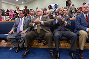 North Charleston Mayor Keith Summey (center) listens to Rev. Al Sharpton address a healing service at Charity Missionary Baptist Church April 12, 2015 in North Charleston, South Carolina. Sharpton spoke following the recent fatal shooting of unarmed motorist Walter Scott police and thanked the Mayor and Police Chief for doing the right thing in charging the officer with murder.