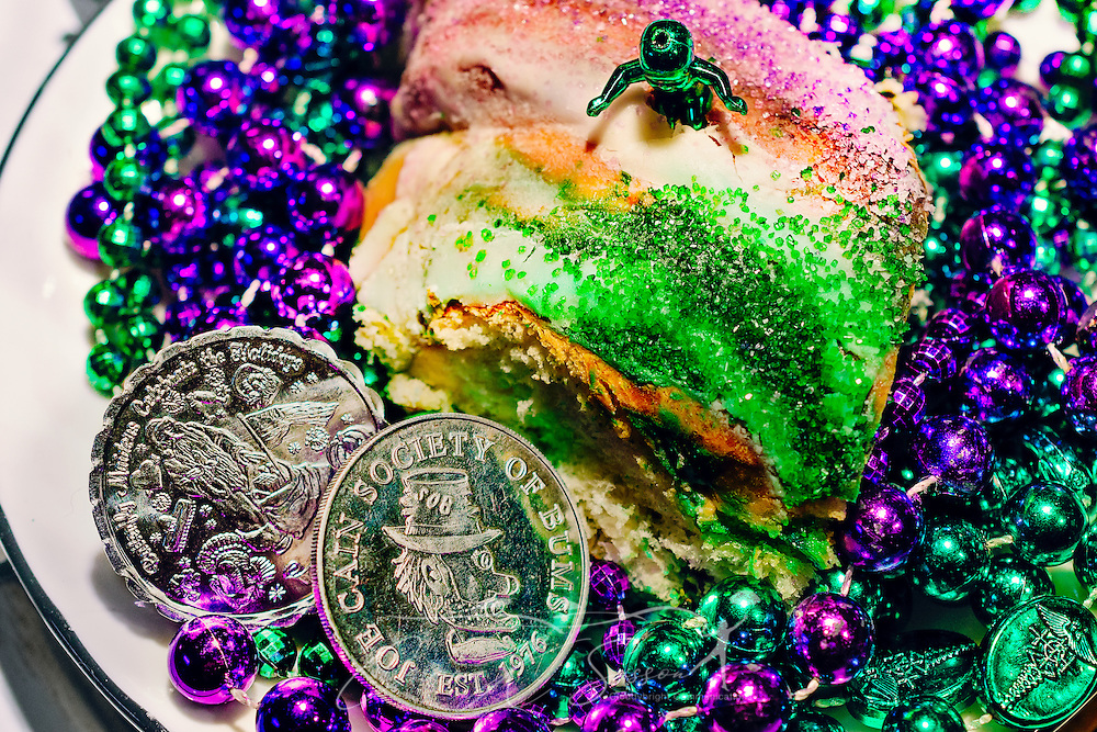 A plastic baby, representing the Christ child, is pictured atop a Mardi Gras King Cake, March 12, 2014, in Mobile, Alabama. Also on the plate are purple and green Mardi Gras beads and two silver doubloons thrown by the Joe Cain Society of Bums. The king cake is traditionally made of fried or baked dough, topped with green, purple, and gold icing or sugar. Modern king cakes sometimes contain fillings such as raspberry, strawberry, cream cheese, or cinnamon. The king cake represents the three kings who visited the Christ child on Epiphany. Doubloons are a popular Mardi Gras throw and are frequently stamped with the date and name of the krewe that throws them. French settlers held the first Mardi Gras in Mobile, Alabama in 1703. Mardi Gras is a season of revelry that extends from Epiphany, 12 days after Christmas, to Fat Tuesday, the day before Ash Wednesday and the beginning of Lent. (Photo by Carmen K. Sisson/Cloudybright).