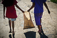 Erni (r),10, and Sida, 8, walking to work at the 'Trash mountain', Makassar, Sulawesi, Indonesia.