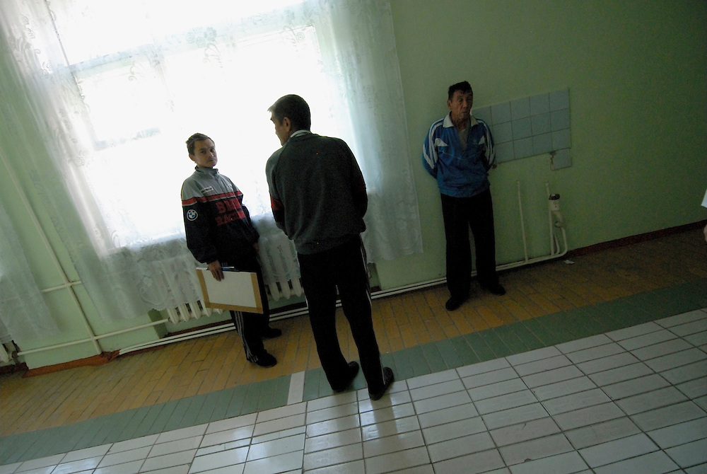 Russia. Tomsk (Siberia). 23.08.2007. TB Hospital. Scene inside corridor. TB patients waiting outside a meeting room where their medical situation will be reviewd by a panel of doctors.