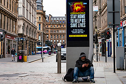 Glasgow, Scotland, UK. 1 April, 2020. Effects of Coronavirus lockdown on streets of Glasgow, Scotland. Homeless man sits beneath video screen with Coronavirus health advice. Iain Masterton/Alamy Live News