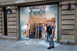 © Licensed to London News Pictures. 09/08/2011. Manchester, UK. Destruction and looting  across the city centre by gangs. Shops are smashed, looted. Swarovski crystal ornament and jewelry shop is smashed and raided. Police stand guard as they tend to an injured man lying bleeding on the ground. Photo credit : Joel Goodman/LNP