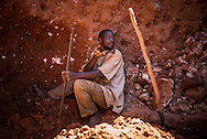 A man digging through some mine waste searching for left over cobalt in a mine between Lubumbashi and Kolwezi, May 31, 2015. AFP PHOTO/FEDERICO SCOPPA