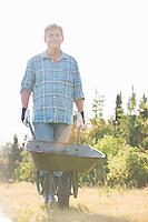 Portrait of male gardener pushing wheelbarrow at garden