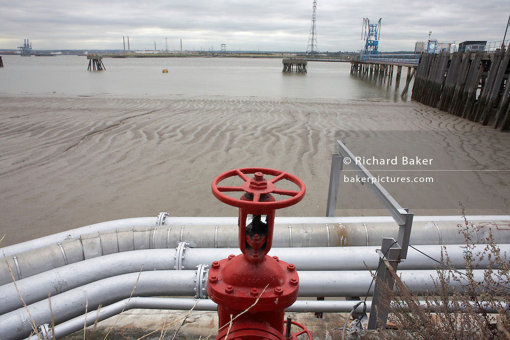 Industrial pipes and red gate valve situated on the River Thames mud at low-tide on an overcast day at Grays, Essex