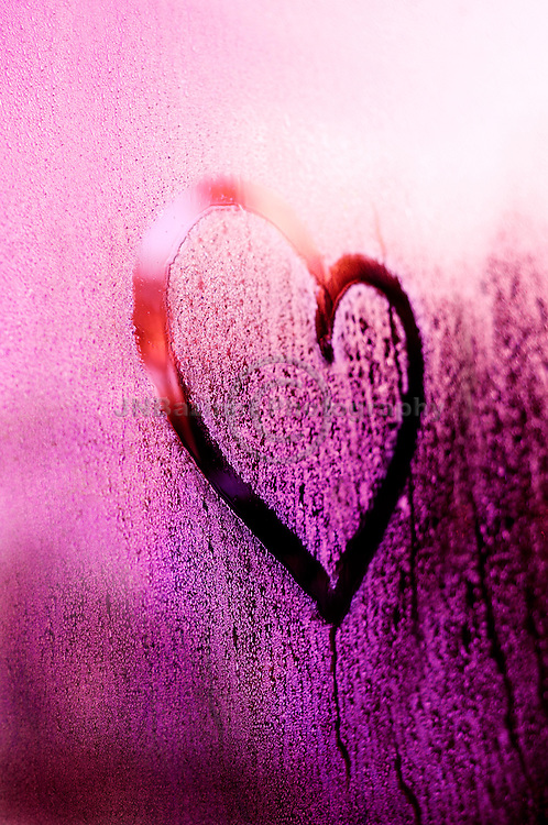 Heart shape drawn on window condensation in purple and pink hues.