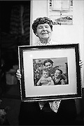 .A woman holds a framed photograph of herself and her two sons that live in Canada she hasn't seen them in over thirty years. Many people escaped communism never to come back..From Neighborhoods series