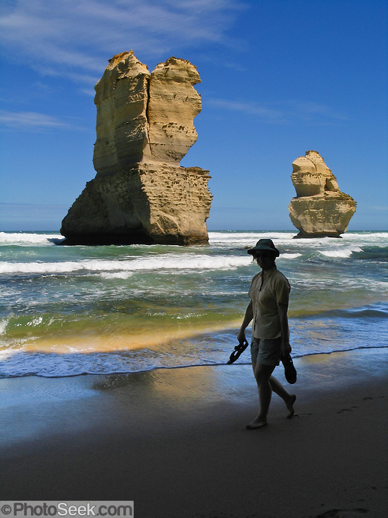 "A woman walks barefoot on the beautiful wild beach at Gibson Steps, near sea stacks ""Gog and MaGog,"" in Port Campbell National Park, Victoria, Australia. Twelve Apostles Marine National Park protects a collection of miocene limestone rock stacks in the Indian Ocean (or Southern Ocean according to Australian geographers), offshore of the Great Ocean Road. The Great Ocean Road (B100) is a 243-km road along the southeast coast of Australia between Torquay and Warrnambool, in the state of Victoria. Dedicated to casualties of World War I, the Great Ocean Road was built by returned soldiers between 1919 and 1932 and is the world's largest war memorial. For licensing options, please inquire."