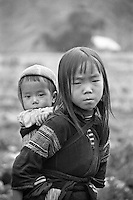 A hilltribe girl works on the fields and takes care of her younger brother