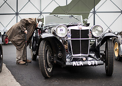 © Licensed to London News Pictures. 28/01/2018. Weybridge, UK. An admirer takes a closer look at a 1933 MG K1 at Brooklands Museum as members of The Vintage Sports-Car Club take part in New Year driving tests round the historic motor racing circuit. Photo credit: Peter Macdiarmid/LNP