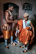 Father helping his son to dress up. Old fashioned retro-styled Bate-Bola, favela of Muquiço, North Zone of Rio de Janeiro, Carnival 2018. Retro Bate-bola are a tendency since the economic crisis in Brazil.
