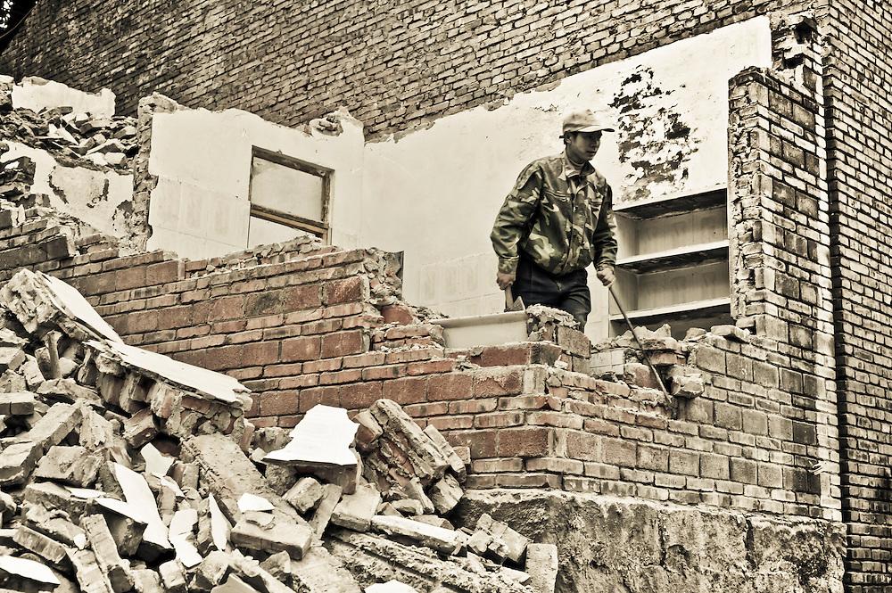 CHONGQING, CHINA - DEC 29, 2010: a man manually demolishes a house near Dan Zi Shi