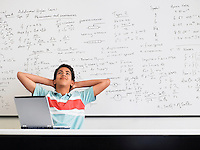Teenage boy sitting in front of whiteboard in classroom