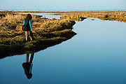JMW Woman walks along waterfront at JMCP with reflections, long sea grasses, blue water