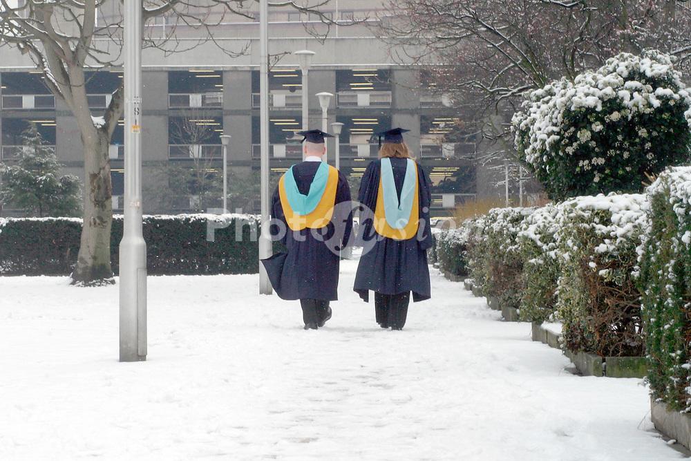 NESCOT college graduates walking in light snow fall Croydon Surrey UK 2005