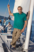 Man Standing on Sailboat with Friends