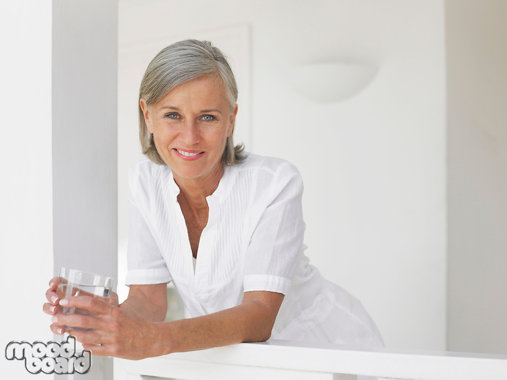 Woman holding glass of water leaning on verandah balustrade portrait