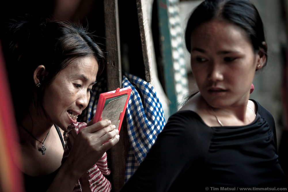 Prostitutes Srey Dah, left, and Srey Leat, right, prepare for a night of sex work in a nearby park in Phnom Penh, Cambodia. She lives with other prostitutes in a downtown slum known for its gangs, pimps, prostitutes, and high rate of HIV.