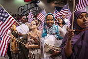 04 JULY 2012 - PHOENIX, AZ:   OMAR YUSUF, left, originally from Somalia, MARGARITA BASRTO, originally from Mexico, SUMAYO AHMED and LAKI SULEMAN, both originally from Somalia, wave American flags after being naturalized as US citizens Wednesay. About 250 people, from 62 countries, were naturalized as US citizens during the 24th Annual Fiesta of Independence naturization ceremony at South Mountain Community College in Phoenix Wednesday. The ceremony was presided over by the Honorable Roslyn O. Silver, Chief United States District Court Judge.  PHOTO BY JACK KURTZ