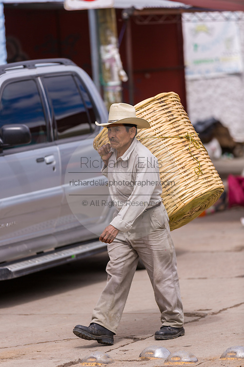 An elderly Zapotec men carries a basket at the Sunday market in Tlacolula de Matamoros, Mexico. The regional street market draws thousands of sellers and shoppers from throughout the Valles Centrales de Oaxaca.