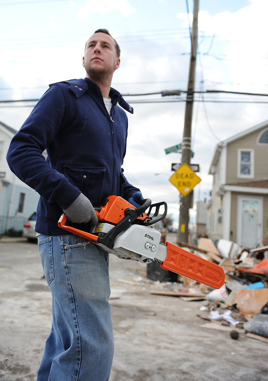 "Dillon Knee wanders with the self-titled ""Broad Channel Police Department"", a rag tag crew of Broad Channel residents who banded together to provide muscle in the clean-up effort of their neighborhood heavily hit by Hurricane Sandy, Nov. 3, 2012."