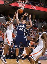 Xavier center Kenny Frease (32) grabs a defensive rebound from Virginia forward/center Jerome Meyinsse (55).  The #22 ranked Xavier Musketeers defeated the Virginia Cavaliers 84-70 at the John Paul Jones Arena on the Grounds of the University of Virginia in Charlottesville, VA on January 3, 2009.