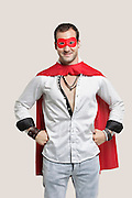 Portrait of young man in superhero costume with hands on hip standing against gray background