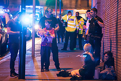 © Licensed to London News Pictures. 22/05/2017. Manchester, UK. Wounded people on Hunts Bank outside Victoria Station and the stairs leading to the Manchester Arena . Police and other emergency services are seen near the Manchester Arena after reports of an explosion. Police have confirmed they are responding to an incident during an Ariana Grande concert at the venue. Photo credit: Joel Goodman/LNP