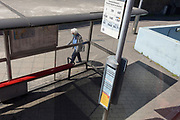 As the UK's Coronavirus death toll during the government's social distancing lockdown, rose by 384 to 33,998, and the R rate of infection is reported to be between 0.7 and 1.0, an elderly lady walks on her own past a bus stop in Waterloo, on 15th May 2020, in London, England.